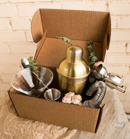Stay at home bar cocktail party, bartender stuff accessories delivery parcel in a natural brown craft cardboard box. A gift to mixology lover. Beige brick wall background. Tender retro hipster colors.