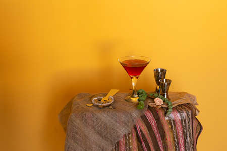 Classic Red Pink Manhattan Cosmopolitan Martini glass cocktail and bartender accessories. Bright yellow background. Stay at home cocktail party or bar website blog content. Copy space for text.