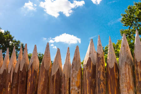 Traditional Slavic Russian Belarus rustic country round log spike fence. A photo background in summer sunny day with green trees warm weather and blue sky