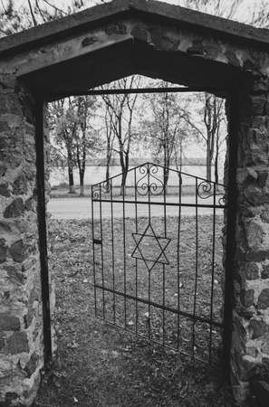 Old ancient historical Jewish cemetery open door gate with a Star of David. A black and white photo with dark gloomy atmosphere.