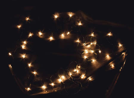 Heart shaped New Year Christmas Holiday celebration light garland on black background. A frame with free blank copy space for text. Good for romantic Valentines day cards, invitations or posters Stockfoto