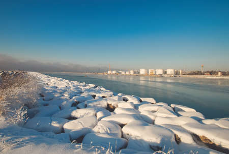 Curonian spit pier with protecting barrier rocks, industrial port docks covered by snow. Beautiful sunny weather and blue sky. Klaipeda Lithuania 版權商用圖片