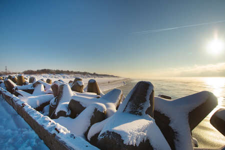 Curonian spit pier with protecting barrier rocks, dunes and an empty beach covered by snow. Beautiful sunny weather and blue sky. Klaipeda Lithuania