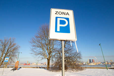 Translation from Lithuanian Zone or Area. Parking zone road sign covered by snow and icicles in a sunny frosty cold January winter day in front of Klaipeda city view