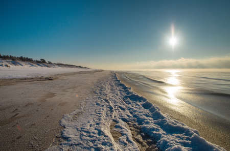 Snow Curonian Spit dunes in January winter sunny day. Blue sky and sea, no people on the beach, calm and beautiful view. Near Klaipeda city in Lithuania 版權商用圖片