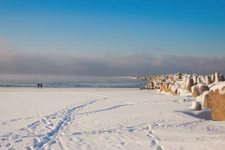 Curonian spit pier with protecting barrier rocks covered by snow. Beautiful sunny weather and blue sky. Klaipeda Lithuania,