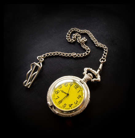 Old vintage retro antique beautiful silver pocket watch on a chain isolated on black background flat lay top view.