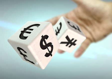 fluctuate: Hand throwing 2 dice with currency symbols. Concept for financial advice, trading, markets. Strong depth of field. Stock Photo