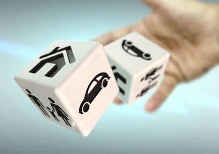 risking: Hand throwing 2 dice with home, family and car symbols. Concept for risking everything you own.