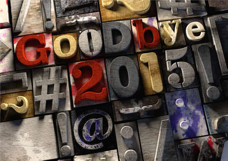 Ink splattered printing wood blocks saying goodbye to the year 2015 and welcoming in the new year 2016. A grunge graphic typography style textured background with moody lighting. Stock Photo