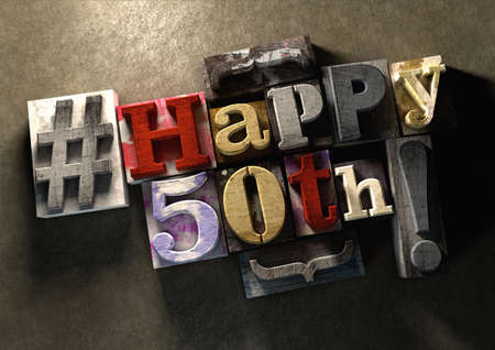 wood blocks: Ink splattered printing wood blocks with grungy Happy 50th birthday typography. Social media hashtag gives a modern edgy graphic design feel. Young and trendy happy birthday title, for use on a best wishes birthday card. Stock Photo