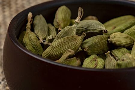 Cardamom in a ceramic cup on a canvas background