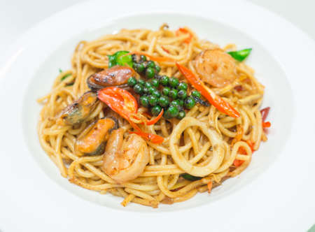 Spaghetti piccanti ai frutti di mare su piatto bianco