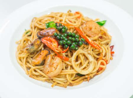 Spaghetti pikantne z owocami morza na białym talerzu