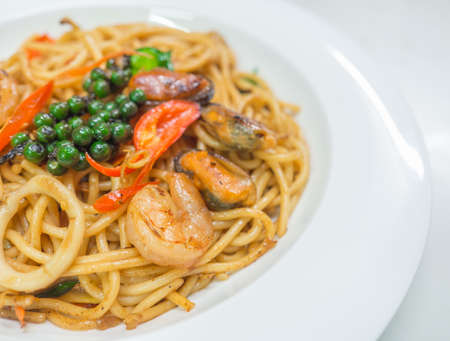 Spaghetti spicy with seafood on a white plate Фото со стока