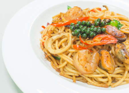 Spaghetti spicy with seafood on a white plate