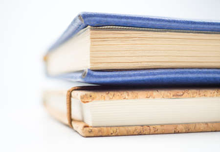 Close-up side view of stack of book on the white background