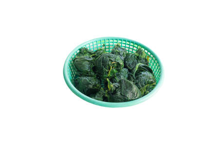 Green spinach in a green basket isolated on white background with clipping path