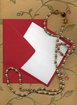 paper sheet and red envelope on textile with necklace Stock Photo - 14163793