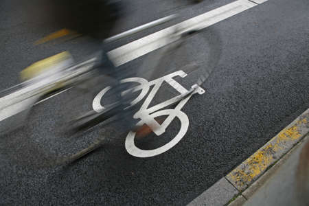 Cyclist passing by at an urban cycle path. Stock Photo