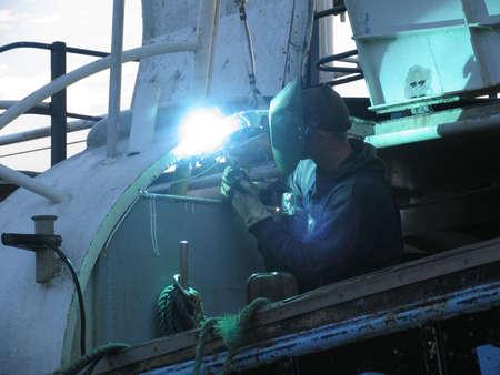 Lasser repareren van een vissersvaartuig Wessel. Stockfoto