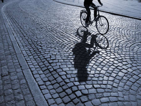 A warm spring afternoon a young man is biking through the old streets of Copenhagen, Denmark. Stock Photo - 4749503