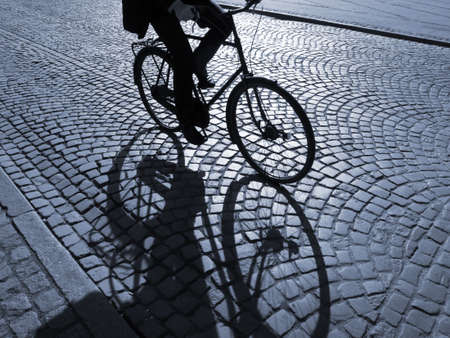 A warm spring afternoon a young man is biking through the old streets of Copenhagen, Denmark.                       Stock Photo