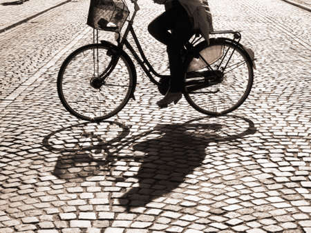 A warm spring afternoon a young girl is biking through the old streets of Copenhagen, Denmark.                       Reklamní fotografie