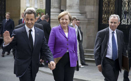 PARIS, FRANCE - JUNE 11 - 2009: French president Nicolas Sarkozy (waving) and German chancellor Angela Merkel (C) outside the Elysee Palace on their way to lunch. Editorial