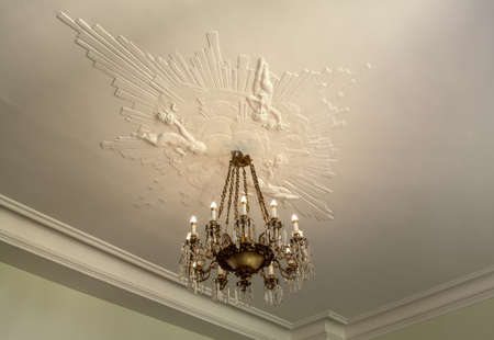 Nice vintage ceiling with old chandelier and beautiful artistic stucco.