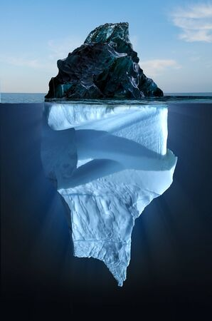 Iceberg floating in the ocean, both the tip and the submerged parts are visible. Top part is smaller than bottom. Not what it seems.