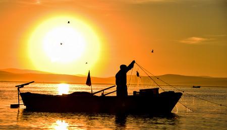 Sunrise and fisherman work