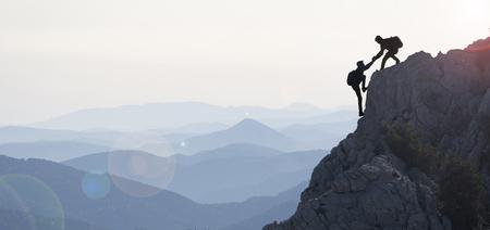 El concepto de cooperación y escaladores cerca de la cumbre