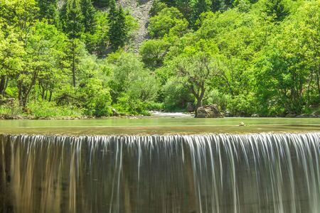 the waters of the waterfall and wooded area Stock Photo
