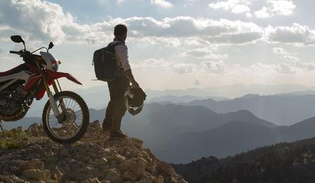 motorcyclist observing the mountain range Archivio Fotografico
