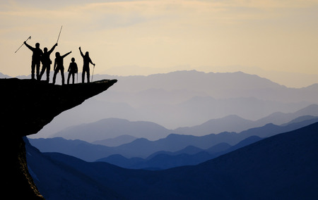 Silhouette of team on the mountain top. Sport and active life