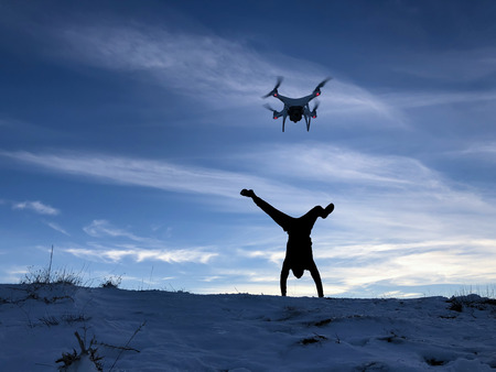Man breakdancing while flying drone during sunset