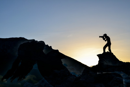 man who takes a picture of cliffs resembling human silhouette
