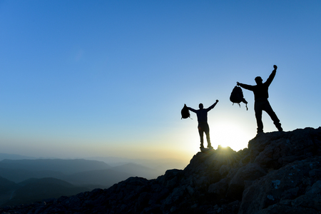 Hiker with backpack standing on top of a mountain with raised hands and enjoying view Archivio Fotografico