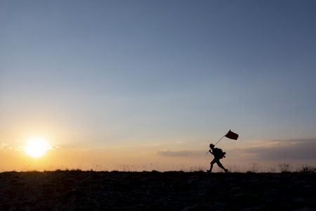 Brave mountaineer carrying the flag on top