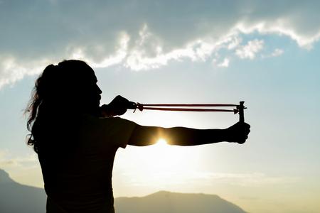 silhouette of man doing slingshot