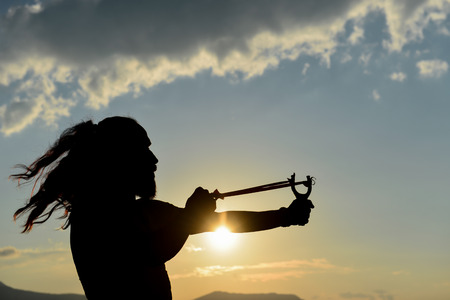 silhouette of man doing slingshot Foto de archivo