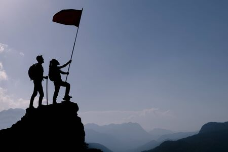 friend holding flag on top mountain. Conception of winner, success and leadership