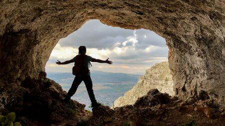 de prachtige grotten op de toppen van de bergen en het geluk van de man die uitkijkt over de stad