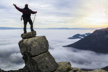 successful climber climbing above fog clouds