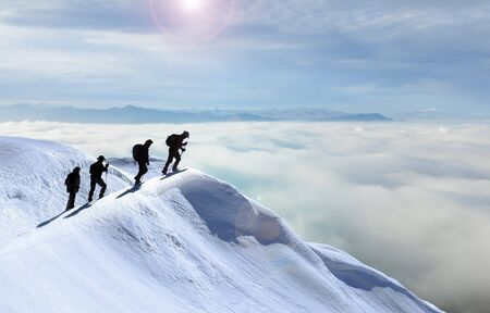 mystical foggy landscapes and summit adventures of four climber friends Stock Photo