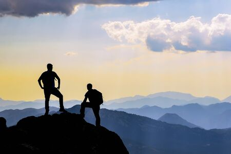 people watching the scenery from the summit and their proud, successful stances