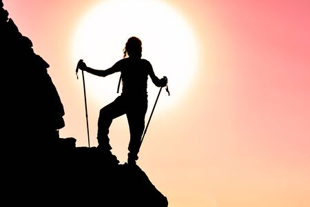 silhouette of successful climber at the top