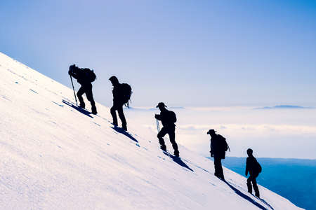 Mountain climbers on snowy slope in winter