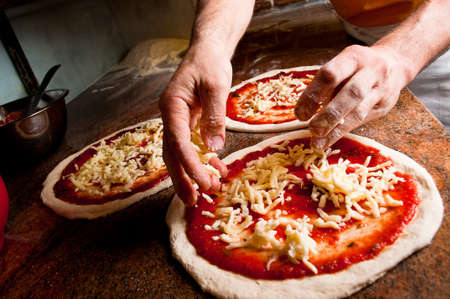 Pizzaiolo making pizza at kitchen